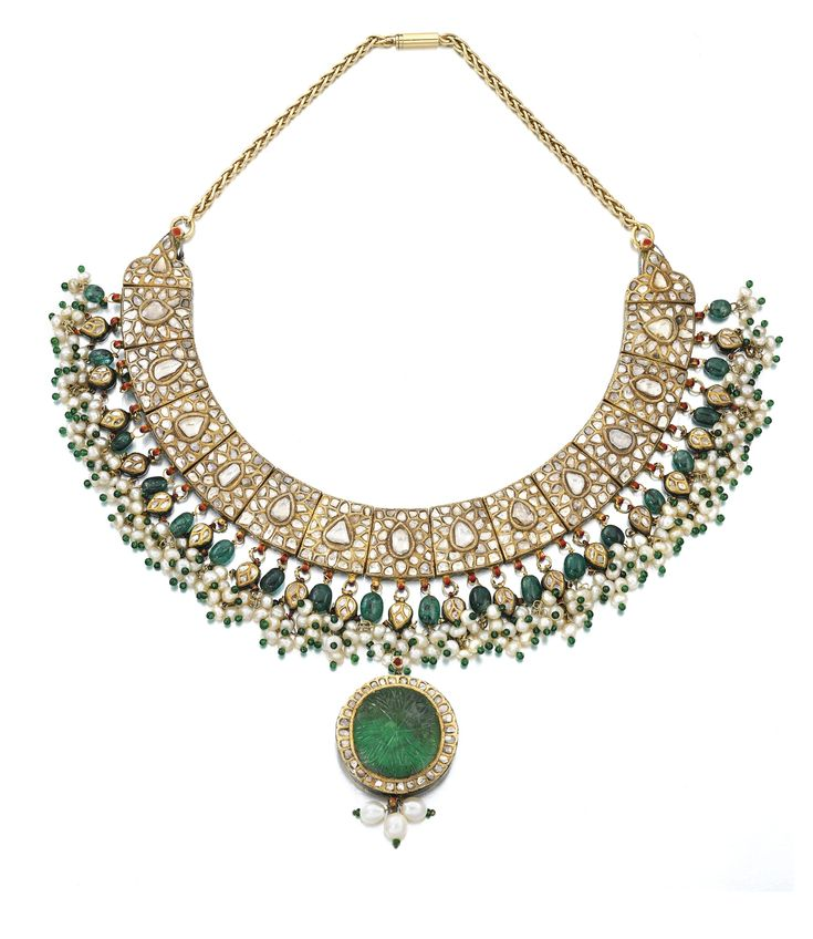 GEM SET, ENAMEL AND DIAMOND PENDENT NECKLACE, RAJASTHAN. Designed as a series of links set with flat-cut diamonds, suspending a fringe of seed pearls and polished emerald beads, some inset with diamonds, the detachable pendant at the front set with a carved paste stone encircled with diamonds, the reverse of the necklace decorated with bird, floral and foliate motifs decorated with safed chalwan enamel, length approximately 380mm.