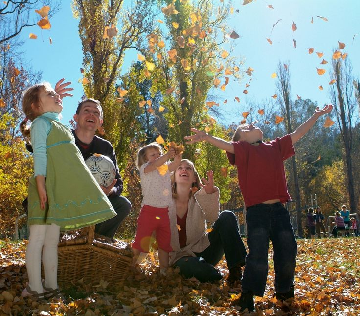 Family playing in the Autumn leaves