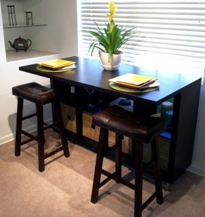 A counter-height eating area that also serves as a desk, work, and storage area for projects.  Hacked from various Ikea parts.