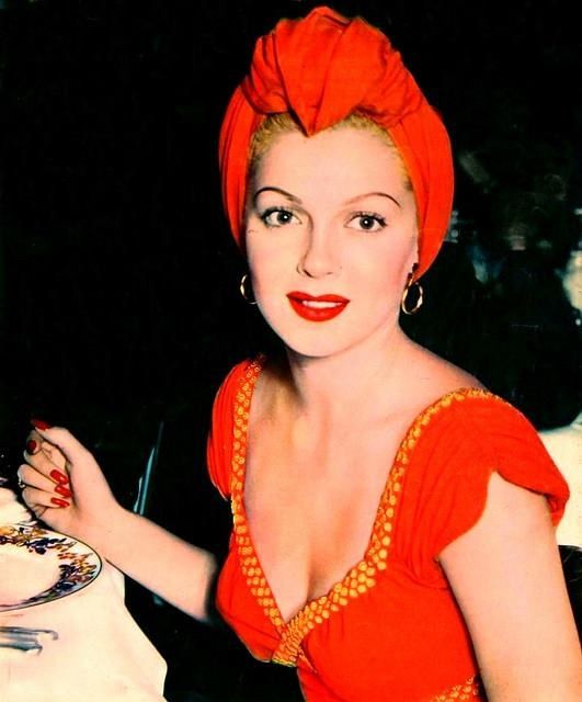 Lana Turner 40s 50s hollywood movie star glam color photo print red dress evening gown turban short sleeves low cut hoop earrings vintage fashion style