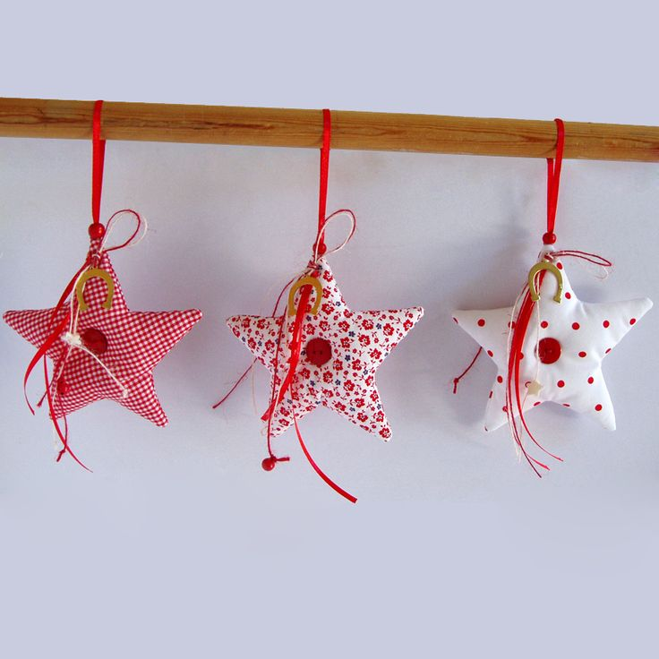 Fabric, hanging star charm decorated with buttons and metallic horseshoes for good luck, in 3 different red shades.