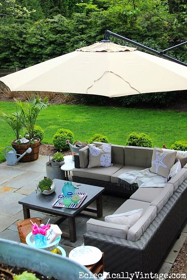 A plain patio becomes an outdoor oasis with some TLC & fresh outdoor furniture and accessories. Kelly from Eclectically Vintage reveals this beautiful patio makeover. We can't get enough of that concrete topped coffee table!