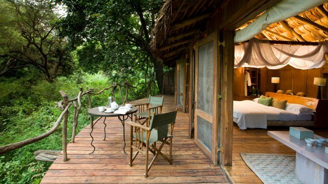 Lake Manyara Tree Lodge, Lake Manyara - TANZANIA. In a lush groundwater forest of ancient fig and mahogany trees, Lake Manyara Tree Lodge allows you to feel totally at one with this green wonderland.