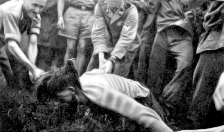 "Waffen SS troops deal swift ""justice"" to a Slovenian partisan with an ax. Note the one German kicking the victim as the ax drops on his neck. The scene is attended by many Waffen SS soldiers."