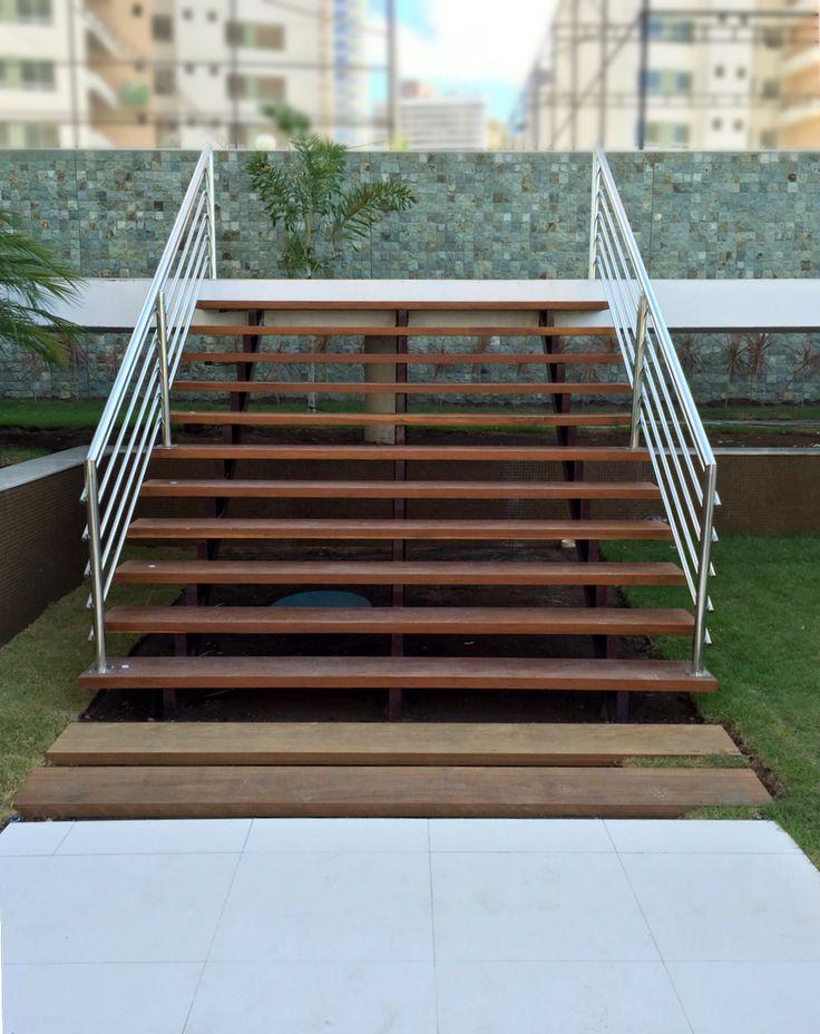 Área de lazer em prédio com escada de degraus e estrutura em madeira destacando-se em meio a vegetação.