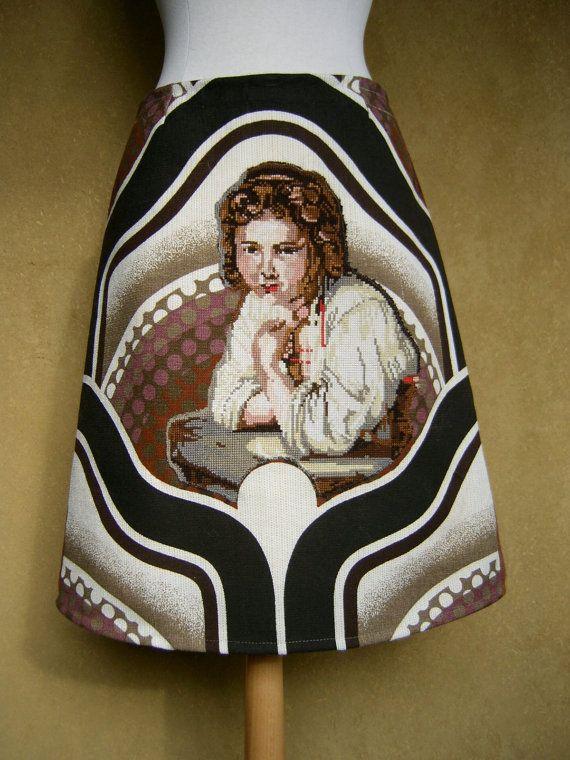 Rechte rok gemaakt van een vintage gordijn, borduurwerk, geruite stof en voering.  De rok is gemaakt van een eclectische mengeling van stoffen en borduurwerk. Het borduurwerk is op een fantastisch stuk Jaren Zeventig gordijn genaaid. Ik ben dol op dit soort grote patronen en de gebruikte kleuren zijn een perfecte match met het borduurwerk.  Het borduurwerk is van Rembrandt en heet Meisje aan het Venster. De gordijn stof voorziet haar van een heel nieuw venster.  De achterzijde van de rok is…