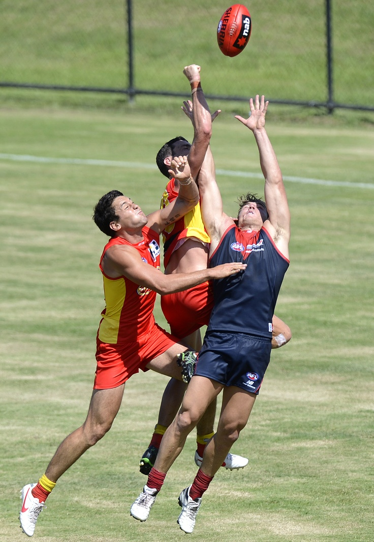 Greg Broughton of the SUNS and Luke Tapscott of the Demons challenge for the ball during the 2013 NAB Cup practice match between the Gold Coast SUNS and the Melbourne Demons at Southport Sharks, Gold Coast.