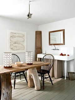 The ship-door dining room table makes this coastal dining room unique and cozy | Photo: William Abranowicz | myhomeideas.com