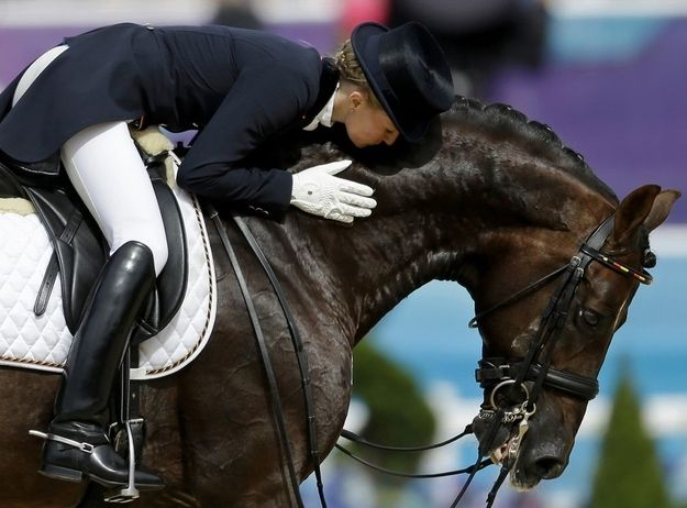 Germany's Helen Langehanenberg kisses Damon Hill, her horse, after they compete in equestrian dressage.
