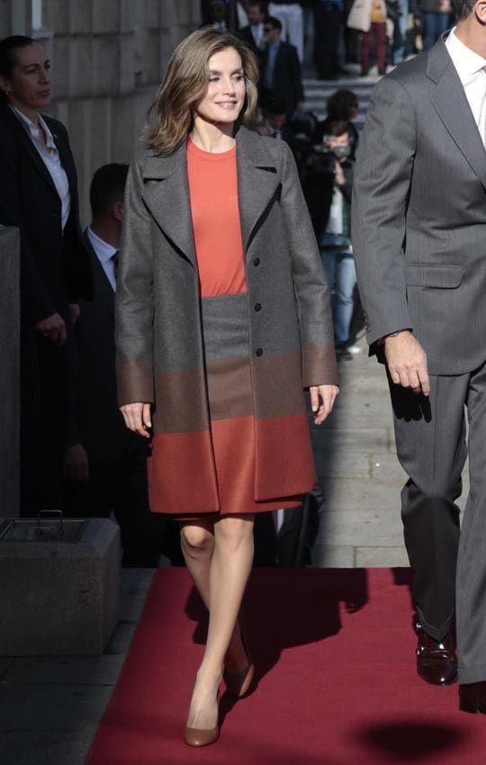 29 de noviembre de 2016. Para su segundo día en Portugal, Doña Letizia ha optado por uno de sus diseñadores de cabecera. Hugo Boss firma este estilismo compuesto por una falda de lana virgen en tres colores: gris, marrón y teja, y lo combina con un abrigo a juego y un jersey de punto en tono caldera.   El bolso de piel marrón también es de la marca alemana y para el resto de accesorios se decanta por firmas españolas: pendientes dorados de Bimba y Lola y salones con el tacón dorado de