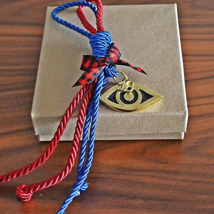 Ένα μπρούτζινο χειροποίητο μάτι, τρισδιάστατο, με μεταξωτά κορδόνια κόκκινα και μπλε , για να μην σας πιάνει το μάτι.