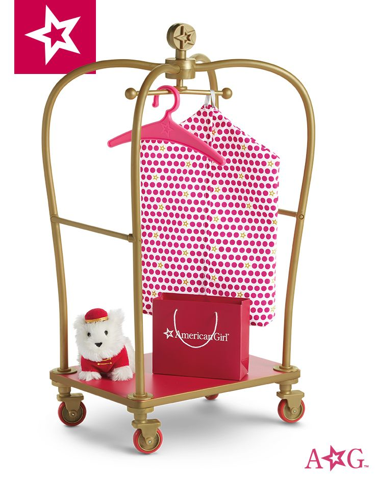 Upon arrival at the hotel, an adorable furry bellhop with a fancy cart is ready to assist guests to their room. The cart features easy-rolling wheels, a hanging bar that swivels, an American Girl shopping bag, a garment bag, and helpful Coconut wearing a charming red hat and jacket. $50