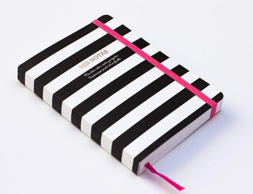 Libreta con portada de rayas blancas y negras e interior rayado. Cuenta con goma elástica en rosa y marcapáginas del mismo color. Papelería bonita.