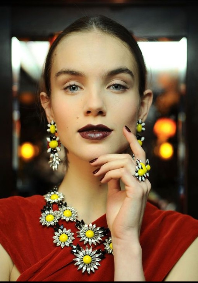 Blood-red pout, daisies round her neck