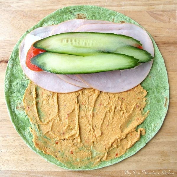 turkey wrap - hummus, cucumber, tomato and turkey on spinach wrap-