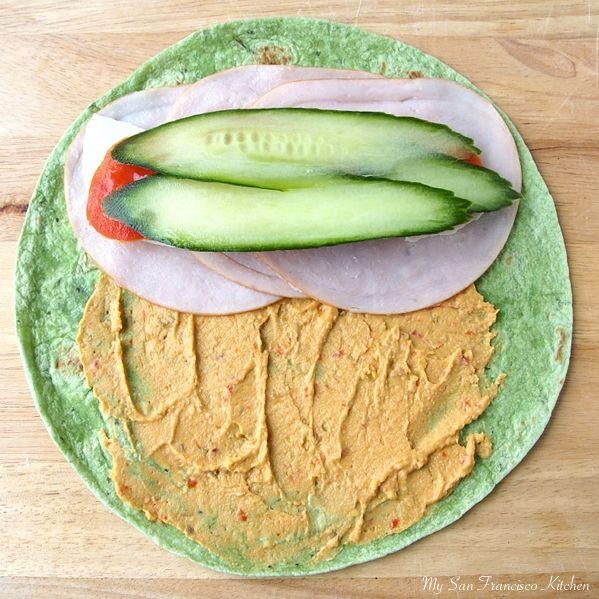 turkey wrap - hummus, cucumber, tomato and turkey on spinach wrap