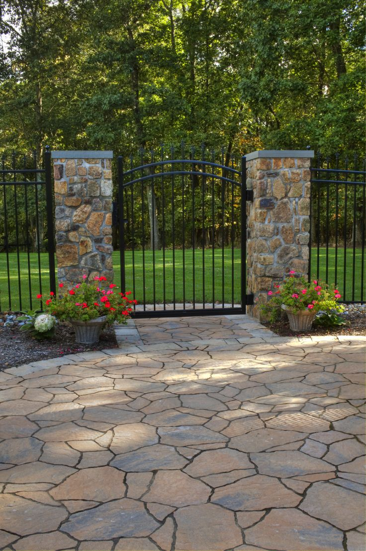 Stone And Iron Gate Entrance Onto Stone Patio Backyard