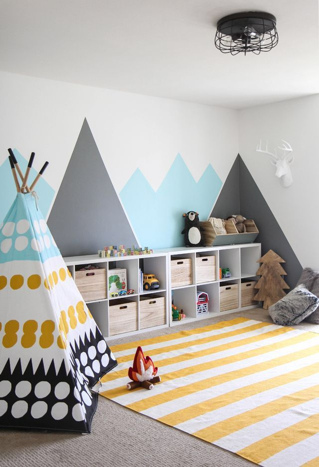Colourful kids playroom. Teepee, tent for playing, mountains painted on walls, yellow stripped rug.