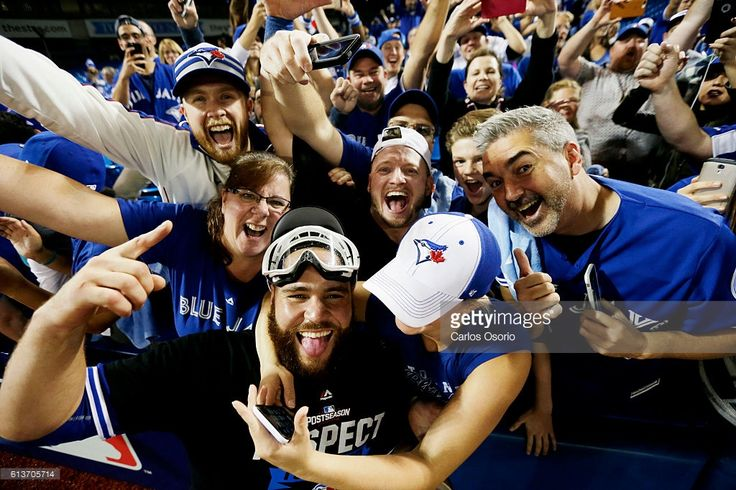 TORONTO, ON - OCTOBER 9 - Blue Jays catcher Russell Martin and 3B Josh Donaldson celebrate with fans after the Toronto Blue Jays defeated the Texas Rangers 7-6 to advance to the ALCS at Rogers Centre on October 9, 2016.