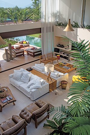 casa mangaratiba   projeto: miguel pinto guimarães   sala de estar com sofás, mesas de centro, luminárias de mesa e par de cadeiras da interni   foto andré nazareth