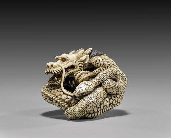 CARVED IVORY NETSUKE: Dragon & Snake. Very finely carved and realistically, detailed ivory netsuke; of a dragon and snake coiled together.