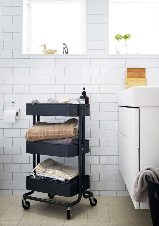 Black rolling cart in a white bathroom with glossy subway tiles.