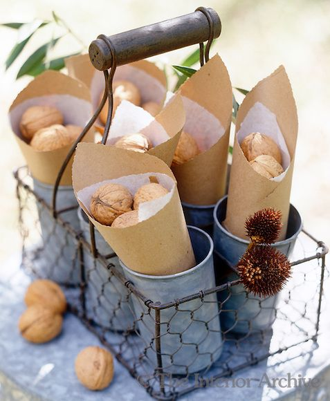 Paper cones filled with walnuts and displayed in a chicken wire basket make simple but individual party favours
