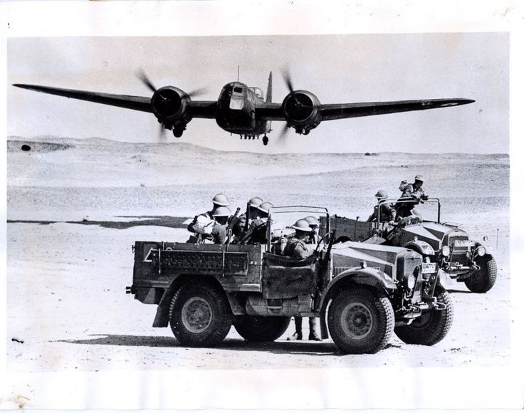A pair of Morris Cormmercials being passed by a low flying Blenheim