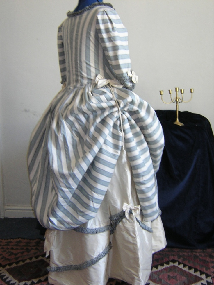 Georgian Polonaise Dress in Raw Silk Blue and Cream Stripe. This is a three-part 18th century Georgian period reproduction gown inspired by one in the Victoria & Albert Museum in London, and made with the help of Janet Arnold's Patterns of Fashion book. In a larger size, it consists of an overdress, matching stomacher and top-petticoat. The gown closes at the front with lacing over the stomacher, & the top petticoat ties around the back & front of the waist with ribbons to give a flexible…
