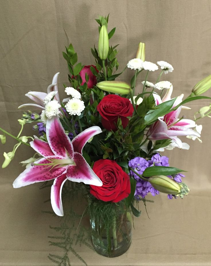 Love Token- red standard roses, pink stargazer lilies, purple stock, white button mum daisies, plumosa, myrtle, and white dendrobium orchids in a cylinder vase
