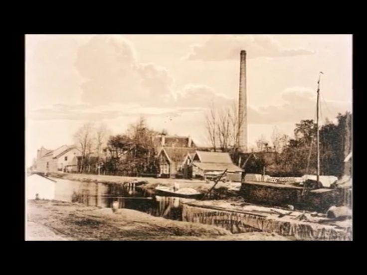 Een foto van het Kanaal met ver op de achtergrond de fabriek van Jansen en Tilanes. Vriezenveen. Twente. Overijssel. Nederland.