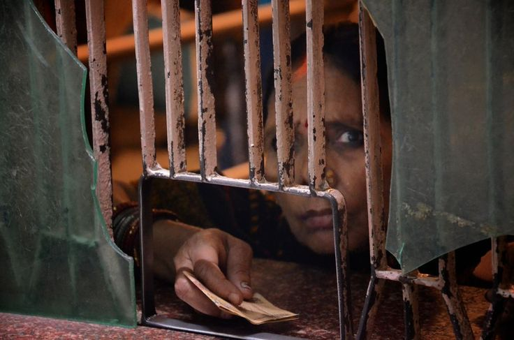 One night, while in line for a last minute train ticket, was invited into the Current Ticket Reservation Office in Gorakhpur Indian Railway Station. With permission, from the other side of the glass, captured this woman, her hand and her money, waiting to pay.
