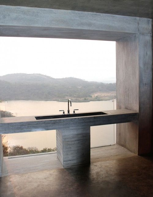 The sturdiness of the concrete frame around the picture window along with the concrete sink, juxtapose strongly as a solid contrast to the view in the distance.