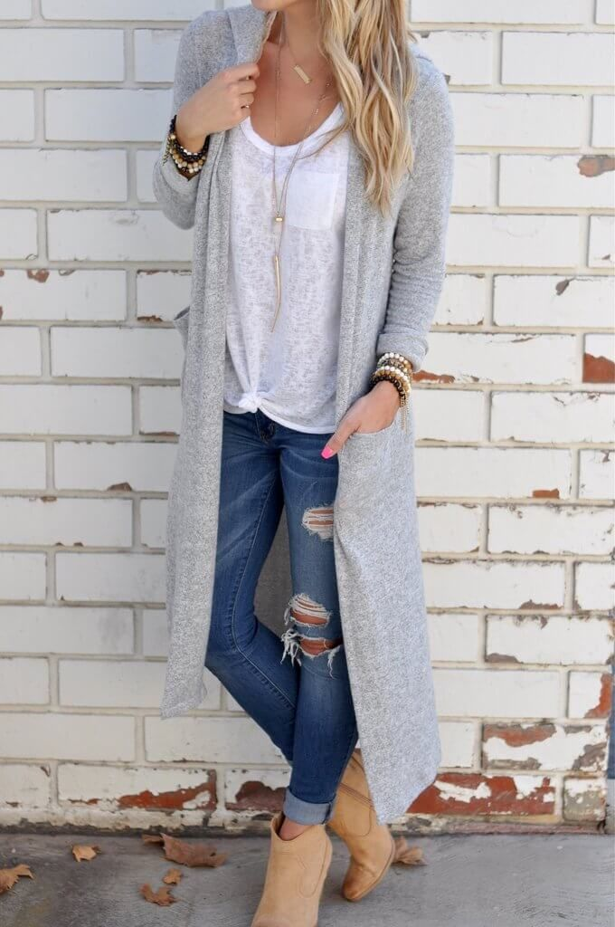 25 Stylish Outfits With Cuffed Jeans: Woman wearing ripped and cuffed skinny jeans with a white T-shirt and long grey cardigan, together with beige ankle booties