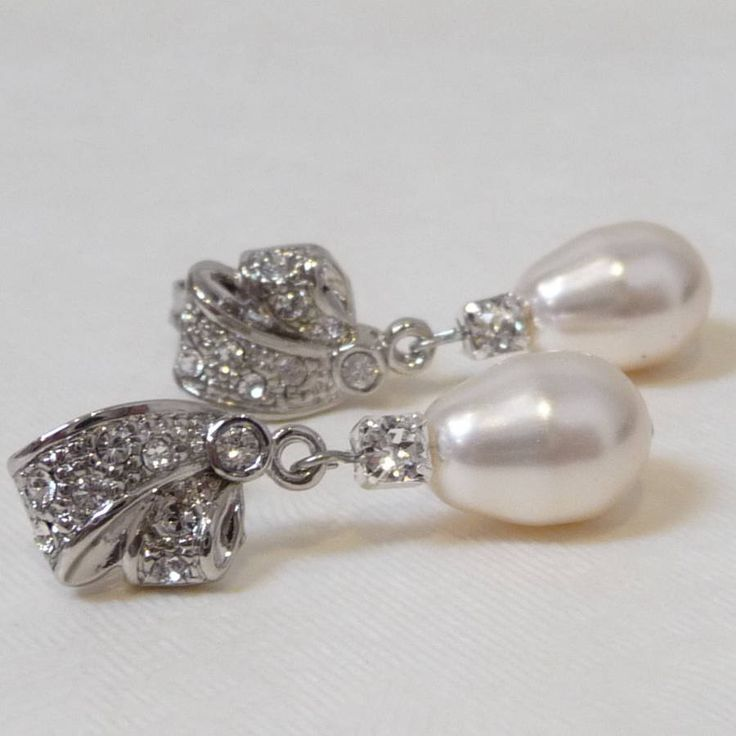 Add a touch of vintage glamour with these heavily embellished teardrop pearl and rhinestone earrings.Available in silver and gold colours.Each earring drop includes a single ivory Swarovski teardrop pearl drop set onto decorative rhinestone embellished studs. If you would like matching accessories then these earrings are designed to go with the following products: - Rhinestone and Teardrop Pearl Pendant Necklace - Vintage Inspired Two String Pearl Bracelet We want to make unwrapping your…