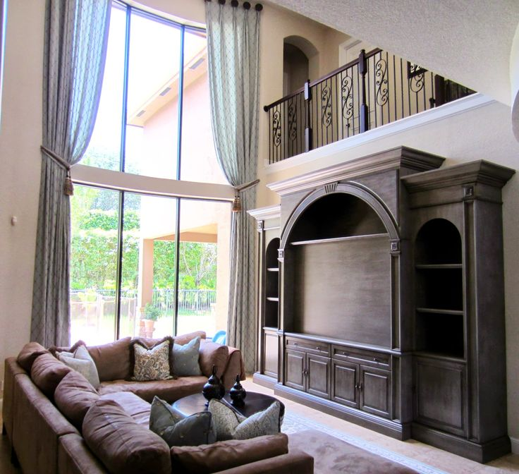 A dramatic custom tv wall unit for a high ceiling living room the custom drapes add a lot for Living room ideas high ceilings