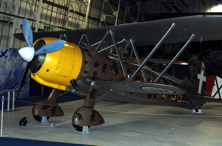 """Fiat CR-42, RAF Museum, Hendon. This aircraft (MM5701) was based in Belgium in th Autumn of 1940 as part of the Corpo Aereo Italiano, the Italian Air Force element involved in the Battle of Britain. On November 11th 1940, flown by Sergente Pietro Savadori, its engine overheated and the pilot made a forced landing on the shingle beach at Orford Ness, Suffolk. It was subsequently test flown by Captain Eric """"Winkle"""" Brown who was impressed by its manoeuvrability noted that it was underarmed."""