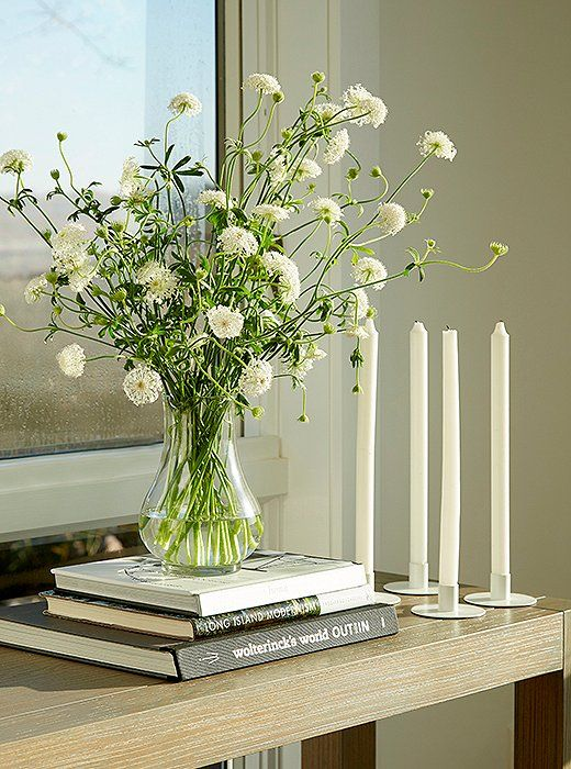 A Parsons-style console in cerused oak is the perfect spot for fresh-cut blooms. Below, two shelves display a few of Foley's many books, the rest of which are downstairs, organized by category.