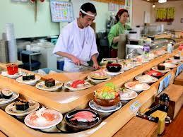 回転寿司 - Sushi rotating around counter.