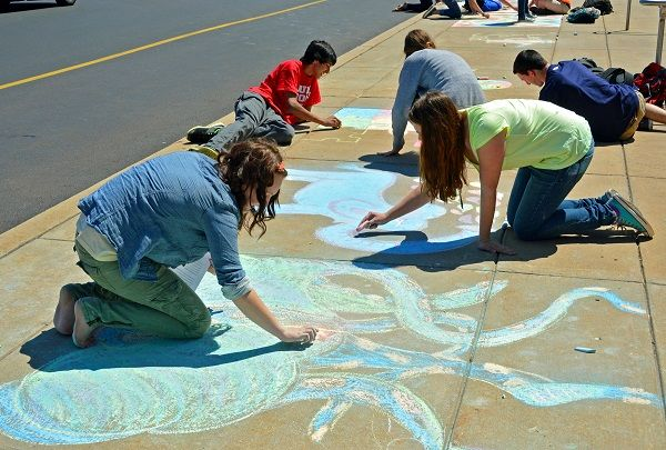 Pennridge High School students decorate the sidewalk outside the school as they celebrate Sidewalk Chalk Day Thursday, April 25. News-Herald photo — DEBBY HIGH