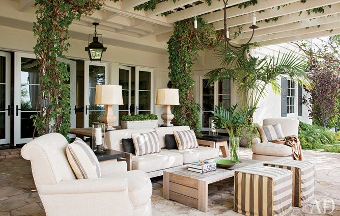 Honeysuckle climbs the trellis of the outdoor living room, which is furnished with Haenisch-designed seating upholstered in Perennials outdoor fabrics; the cocktail table is by Holly Hunt.