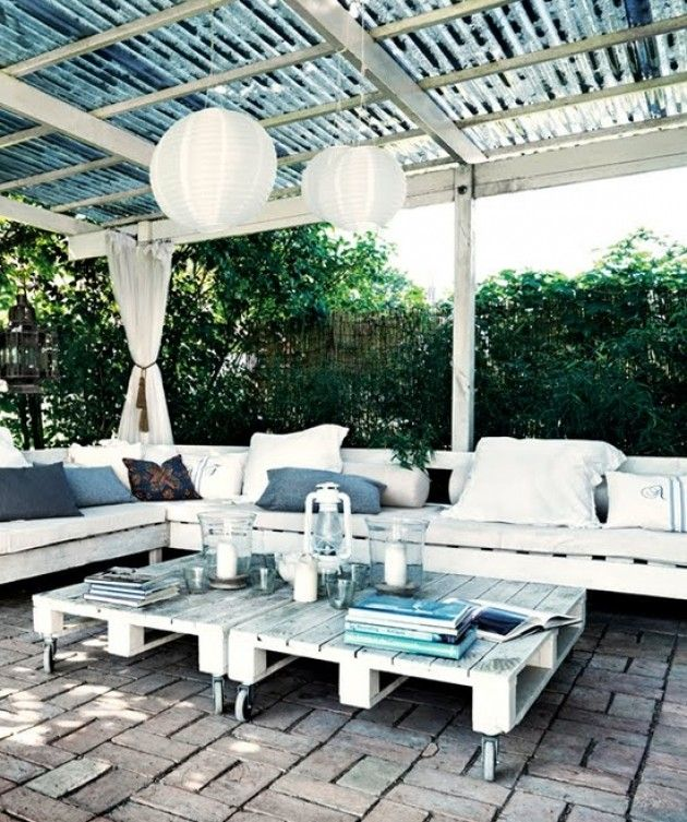 Outdoor patio on a budget….pallets on rollers, galvanized roof, pavers, lanterns