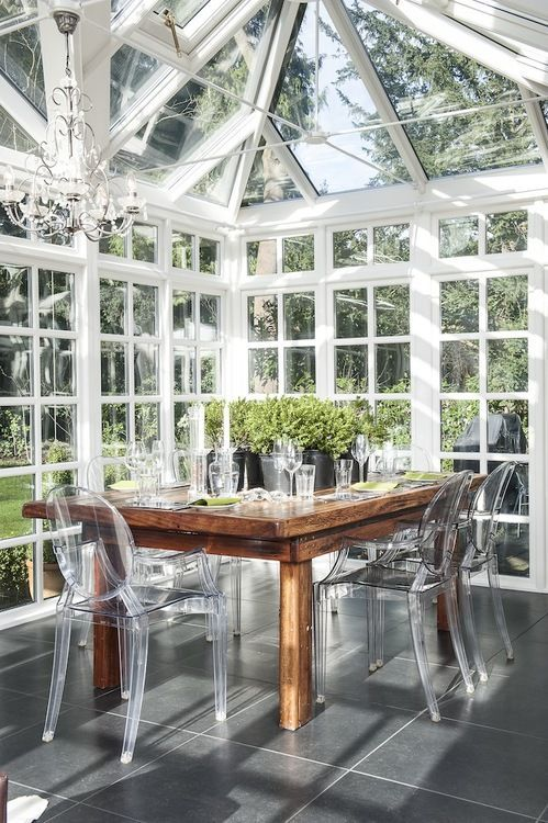 All-glass sunroom with a wood dining table and clear ghost chairs. Wow!