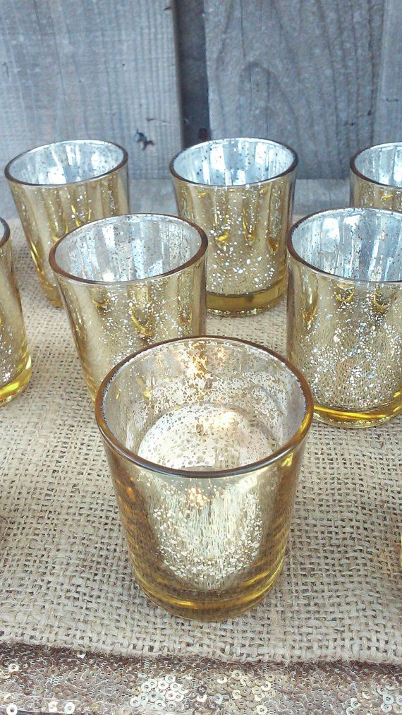 This listing is for a set of gorgeous, glittery, and gold candle holders. These mercury glass candle holders will add elegance and romance to your wedding tables. Imagine your reception lit up with the warm and inviting glow of these flickering candles. A perfect scene for a perfect day!!  These candle holders measure 2.5 tall and 2 in diameter (at the top). They have a speckled gold pattern on the inside of the glass. These can hold a regular tealight or votive candle. The look best with a…