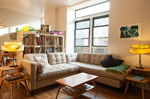 Dividing An Open Room With Sectional Sofas And A Bookshelf