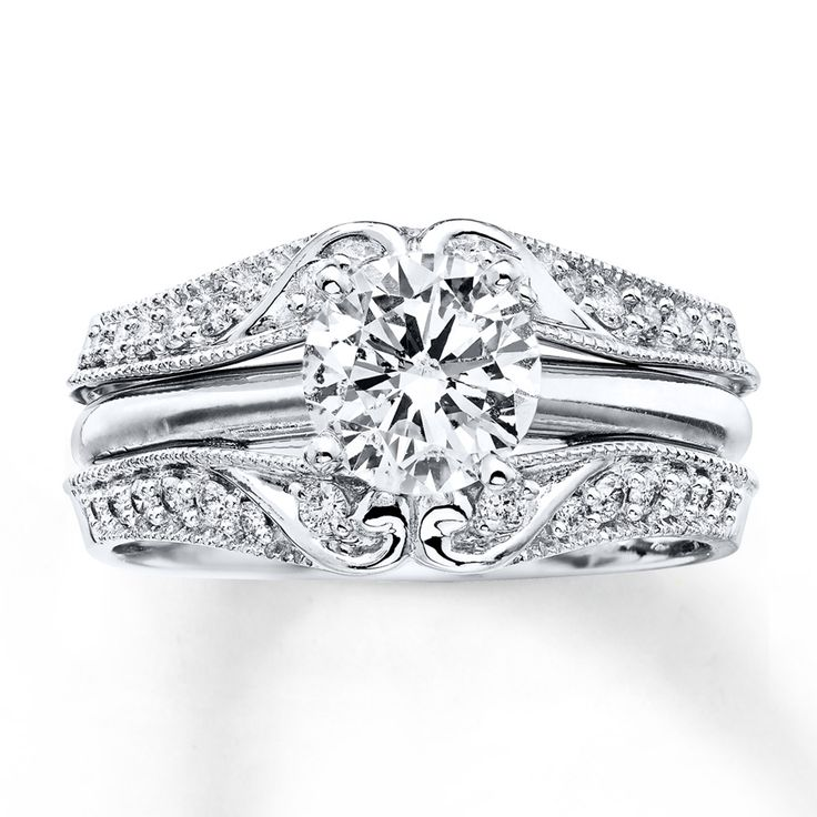 This glorious enhancer ring features tendrils of 14K white gold curling amidst dazzling round diamonds above and below a space for her solitaire engagement ring (sold separately). Milgrain detailing gives the ring a distinctly vintage flair. The enhancer ring has a total diamond weight of 1/4 carat. Diamond Total Carat Weight may range from .23 - .28 carats.