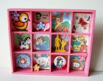 Eine süße Mini Shadow Box aus lackiertem Holz, mit kleinen Spielzeug-Schätze und Kitsch Buttons. Enthält eine winzige keramische Figur und Mini Holz Kokeshi Puppen, ein Vintage Knopf, eine Puppe Hand, ein Spielzeug aus Holz Baum und Keramik Perlen eine Katze und einen Frosch.  Die Seiten sind mit Vintage floral Multifunktionsleiste eingerichtet. Diese Miniatur-Box hat eine Schleife hängen auf der Rückseite oder eigenständig aufrecht.  Misst ungefähr quadratisch 9cm (3,5 Zoll) und 1,5 cm tief…