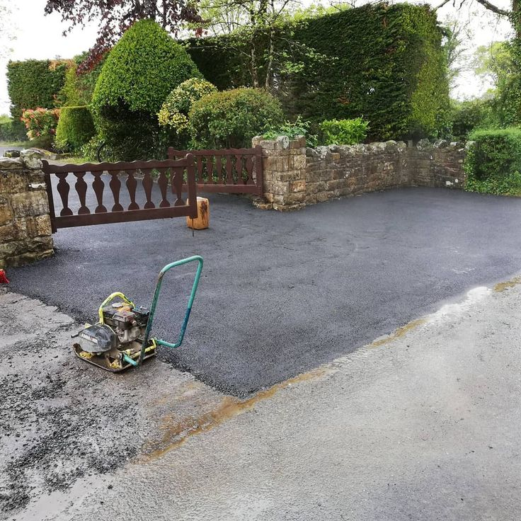 The driveway with worn old tarmac resurfaced with new