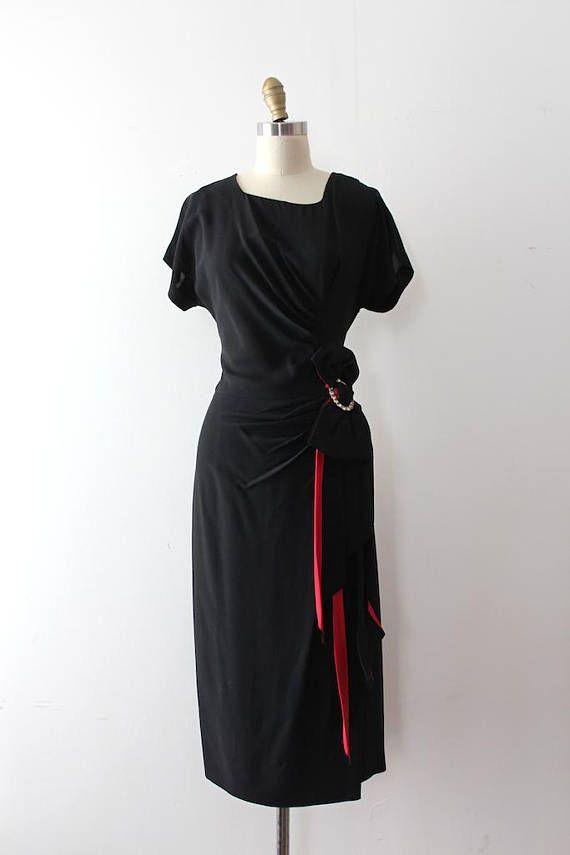 Wunderschöne schwarze Abendkleid aus den späten 1940er / Anfang der 1950er Jahre. Dieses Kleid verfügt über eine schmeichelhafte Silhouette mit einem asymmetrischen Faltenwurf, die führt zu einem Strass-Detail und ein Pop-rot! Label: keine Verschluss: Metall-Reißverschluss Maße: Am besten passt: mittlere ca. Brustumfang: ca. 36 Taille: 30 Hüfte: 43 Länge: 47 Ärmellänge: 8.5 Zustand: fast ausgezeichneten Jahrgang Zustand - Gebrauchsspuren und ein kleine verdammt in der Rock. verkauft....