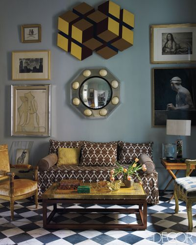 In the sitting room, a steel-and-ostrich-egg mirror hangs above a sofa upholstered in a 1960s David Hicks fabric; the Jacob Frères armchair is covered in a Rubelli velvet, and the cocktail table is from the '70s. The artworks include paintings by Xavier Vilató, bottom left, and José María Yturralde, center, and a Josep Maria Subirachs engraving and Miguel Macaya painting, right. Photographer: Simon Upton